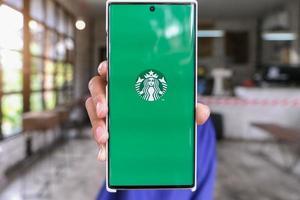 chiang mai, thaïlande 2021- une femme tient un smartphone avec une application starbucks à l'écran photo
