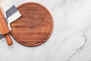 plateau de pizza en bois vide avec serviette mis en place sur pierre de marbre photo