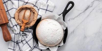 pâte à levure fraîche faite maison crue reposant dans une poêle en fonte photo