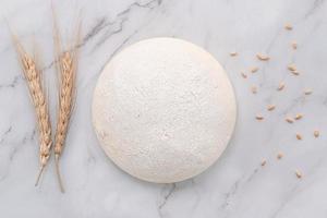 pâte à levure fraîche maison crue reposant sur une table en marbre à plat photo