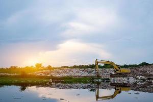 une pelle rétro jaune soulève des ordures à l'usine de tri des déchets photo