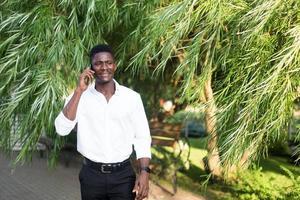 heureux afro-américain avec un téléphone dans la rue photo
