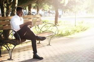 homme d'affaires afro-américain, travaillant sur un ordinateur portable sur un banc de parc, photo