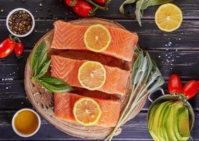 filet de saumon cru coupé en morceaux, poivre sel aneth citron romarin photo