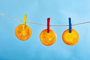 des tranches d'oranges ou de mandarines séchées sont accrochées sur une corde à linge photo
