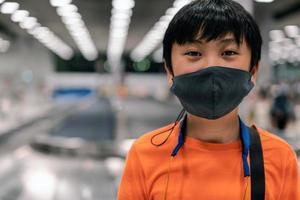 un garçon portant un masque de santé pour voyager à l'aéroport photo