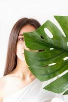 femme tenant une feuille de monstera verte devant son visage photo