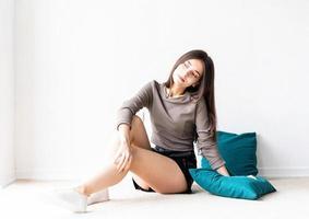 femme dans des vêtements décontractés assis sur le sol avec des oreillers souriant photo
