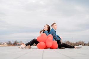 couple assis tenant un tas de ballons rouges passer du temps ensemble photo