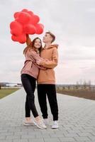jeune couple d'amoureux avec des ballons rouges embrassant à l'extérieur s'amusant photo