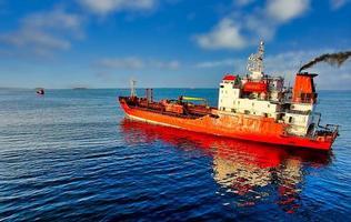 paysage marin avec un bateau rouge sur fond bleu de la mer photo