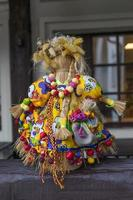 poupée de paille dans un costume en tissu brillant fait par des mains humaines photo