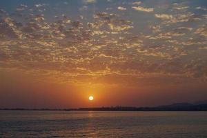 coucher de soleil lumineux sur une mer calme et un ciel coloré photo