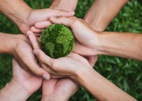Jour de la Terre. mains adultes travail d'équipe harmonie tenant la terre sur les mains photo