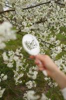 gros plan en plein air de jeune femme main tenant un petit miroir rétro photo