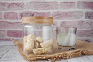 barres d'avoine savoureuses dans un bocal en verre et du lait sur la table photo