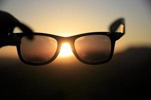 coucher de soleil coloré à travers une paire de lunettes de soleil photo