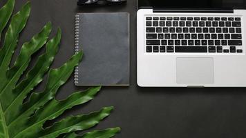 feuilles vertes, ordinateur portable, alarme, cahier, sur, arrière-plan noir photo
