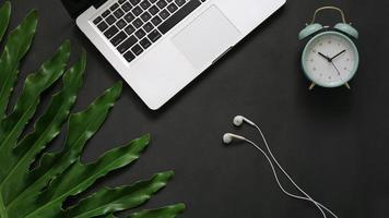 Feuilles vertes pour ordinateur portable réveil écouteur sur fond noir photo