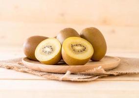 kiwi doré frais en plaque de bois photo