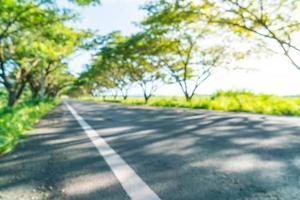 route asphaltée floue abstraite dans la forêt - boostez le style de traitement des couleurs avec effet sunflare photo