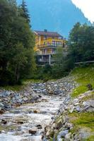 grand chalet à côté d'une rivière de montagne rocheuse. photo