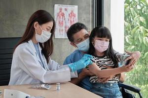 fille asiatique prenant un selfie pendant qu'un médecin est en train de vacciner. photo