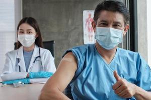 patient asiatique avec masque facial pouce vers le haut avec une femme médecin. photo