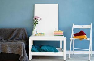 maquette de cadre d'affiche blanc sur une table basse dans une chambre bleue photo