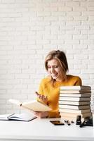 jeune femme souriante en pull jaune lisant un livre et riant photo