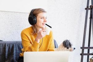 jeune femme souriante dans des écouteurs noirs étudiant en ligne à l'aide d'un ordinateur portable photo