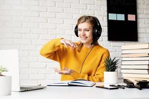 femme au casque étudiant en ligne à l'aide d'un ordinateur portable parlant dans un chat vidéo photo