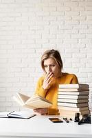 Jeune femme souriante en pull jaune lisant un livre à la surprise photo