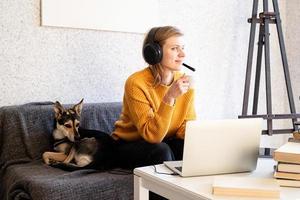 femme au casque étudiant en ligne à l'aide d'un ordinateur portable, buvant du café photo