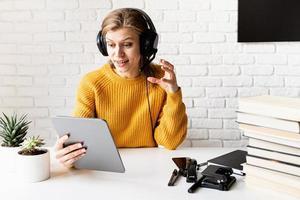 femme au casque noir étudiant en ligne à l'aide d'une tablette numérique photo