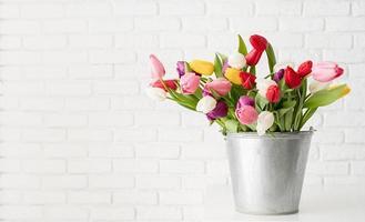 Seau de fleurs de tulipes sur fond de mur de briques blanches photo