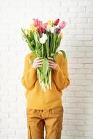 heureuse belle femme en vêtements jaunes tenant un bouquet de tulipes photo