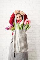 femme tenant un sac en tissu à pois gris avec des tulipes colorées photo