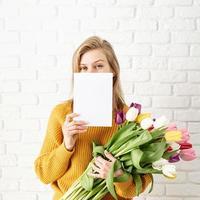 femme en vêtements jaunes tenant un bouquet de tulipes et une carte vierge photo