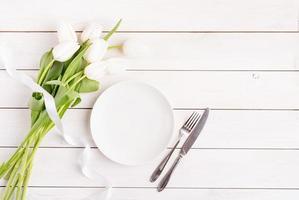 cadre de table de fête en blanc, assiette blanche et tulipes photo