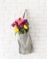 sac en tissu gris à pois rempli de tulipes colorées photo