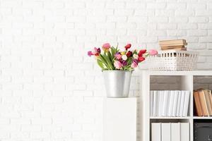 seau de fleurs de tulipes à côté de la bibliothèque photo