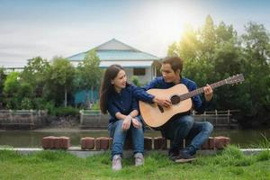 deux personnes amis jouent de la guitare reste en été heureux en vacances photo