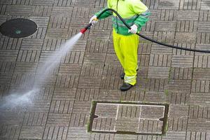travailleur tenant un tuyau nettoyant un trottoir avec de l'eau photo