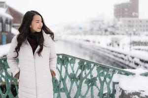femme asiatique souriante heureuse de voyager dans la neige hiver photo