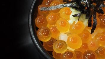 œufs d'ikura de saumon servis avec du riz et garnis d'algues photo