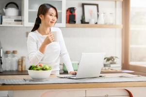 femme asiatique ayant une pause-café tout en travaillant à domicile photo