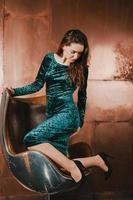 jolie jeune femme vêtue d'une robe bleu velours, sur une chaise photo