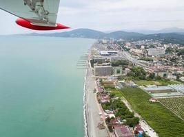 l'aile d'un avion volant au bord de la mer, panorama de la côte photo