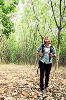 belle jeune femme portant un sac à dos marchant en forêt. photo